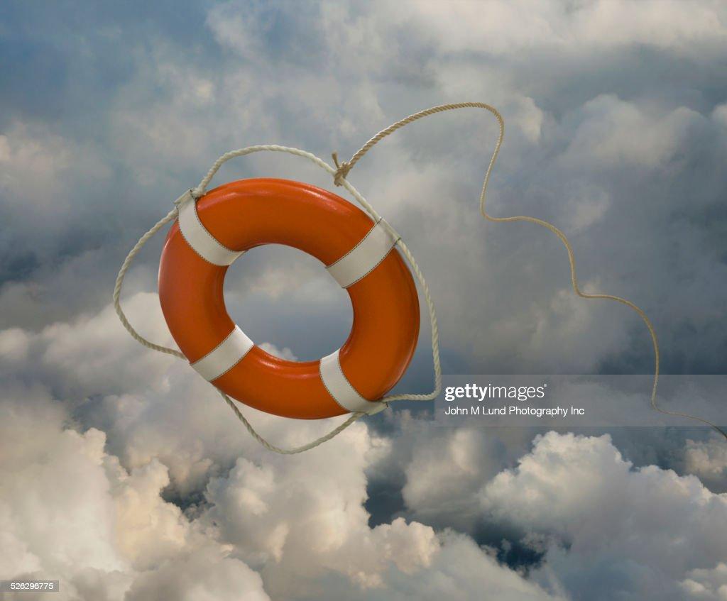Orange life preserver floating in clouds : Stock Photo