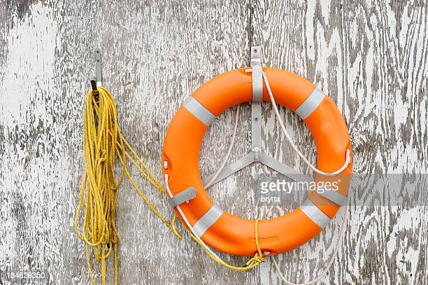 Orange lifebuoy and rope hanging on  weathered gray wooden wall.
