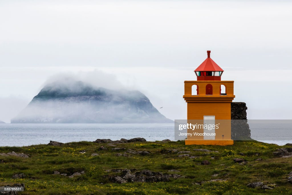 Orange lighthouse on rocky remote cliff : Foto stock