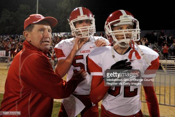 Orange Lutheran High coach Dean Vieselmeyer left explains the plays that are happening on the field to Jake Olson center as teammate Walter Funk...