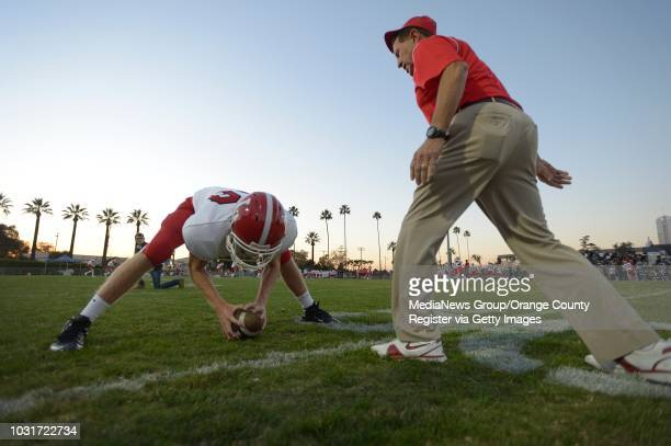 Orange Lutheran High coach Dean Vieselmeyer right works out with long snapper Jake Olson before their game against St John Bosco in Bellflower Olson...