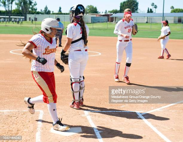 Orange Lutheran's Adrianna Millan scores past Mater Dei catcher Morganne Flores on Maddy Dwyer's triple during the Lancers 51 Trinity League victory...