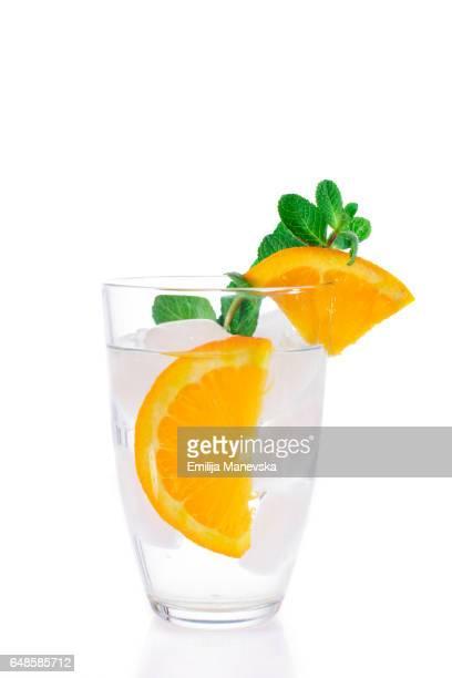 Orange mocktail with fresh mint leaf on white background