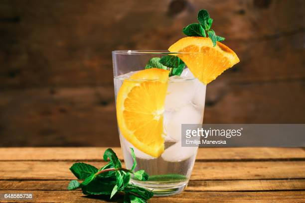 Orange mocktail with fresh mint leaf on wooden background