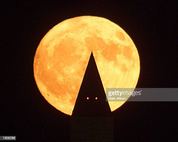 A orange moon rises with the Washington Monument in the forground October 12 2000 in Washington DC There will be a full harvest moon tommorrow on...