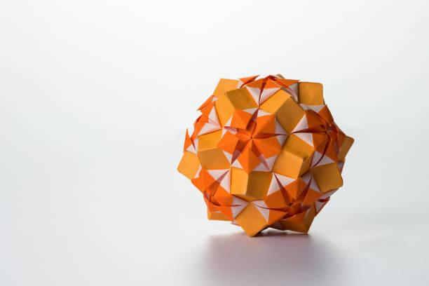 Orange origami on white background, sphere with symmetric pattern