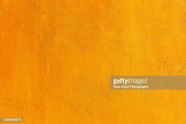 orange painted cement wall background - orange background stock pictures, royalty-free photos & images