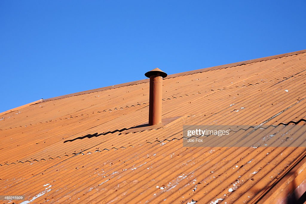 Orange painted metal corrugated roof and chimney : Stock Photo