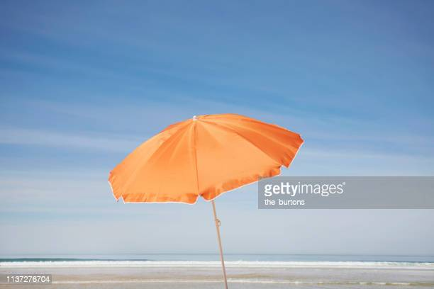 orange parasol on the beach against blue sky - parasol stock pictures, royalty-free photos & images