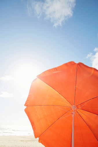 Orange parasol on the beach against sky - gettyimageskorea