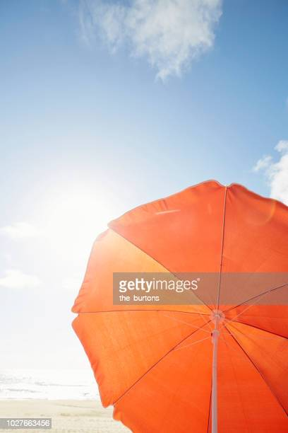 orange parasol on the beach against sky - accesorio personal fotografías e imágenes de stock