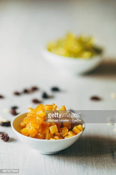 Orange Peel In Bowl By Raisins And Candies On Table