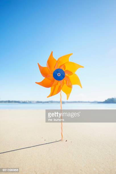 Orange pinwheel on the beach against blue sky