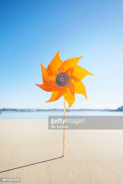 Orange pinwheel on the beach against blue sky