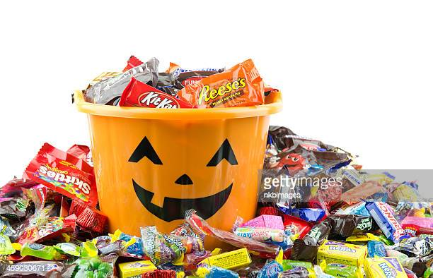 orange plastic halloween bucket filled and overflowing with candy - happy halloween stock photos and pictures