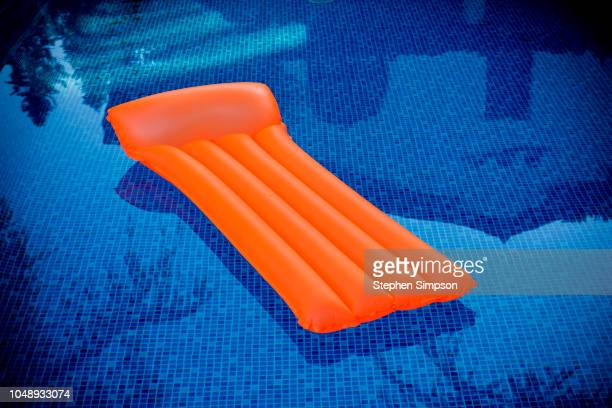 orange plastic raft floats in blue tiled swimming pool - swimming float stock pictures, royalty-free photos & images