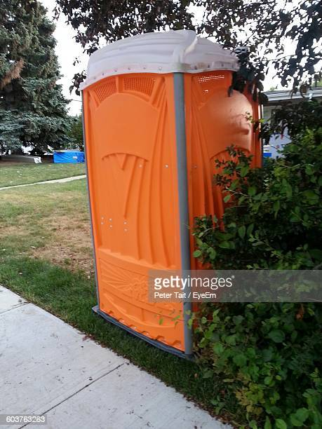 orange public restroom on field - portable toilet stock photos and pictures