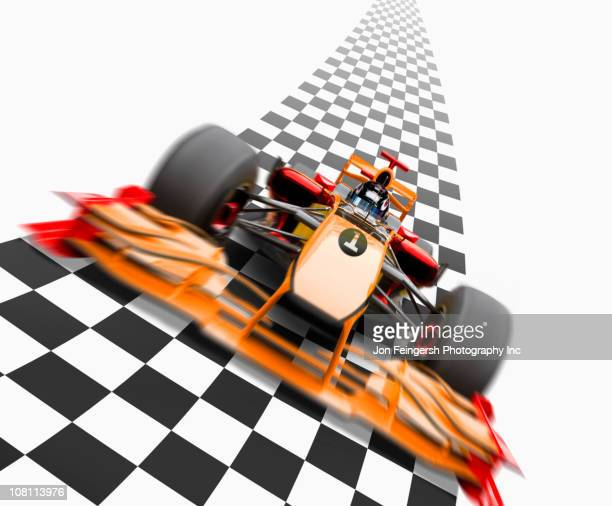 Orange race car driving on checkerboard road