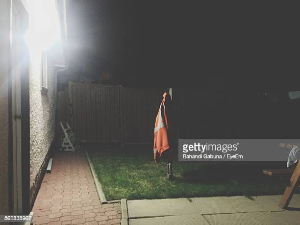 Orange Reflective Protective Suit Hanging On Wooden Post In Back Yard At Night