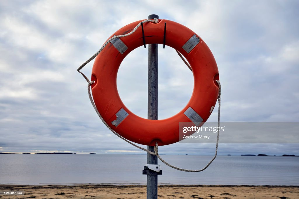 Orange ring buoy with rope on a pole. In the background is the beach, sea and an overcast sky, Oulu, Finland : Stock Photo