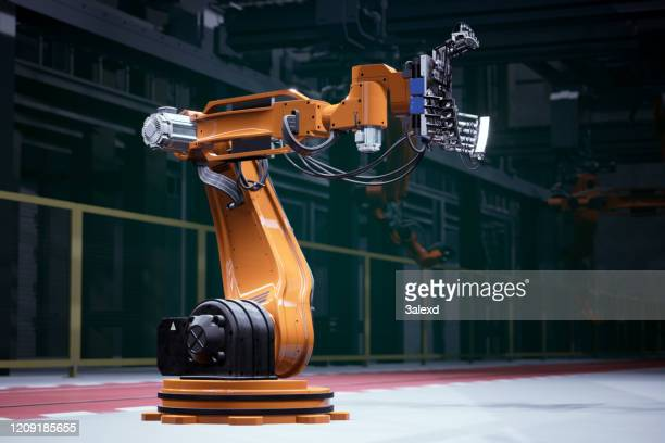 orange robot in a factory - robot stock pictures, royalty-free photos & images