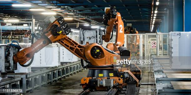 orangefarbene roboterarme arbeiten in einer fabrik - automatisiert stock-fotos und bilder