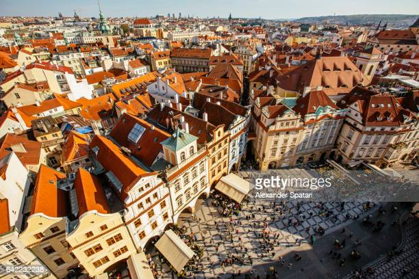 orange roofs of prague old town and town square with tourists seen from above, czech republic - prag stock-fotos und bilder