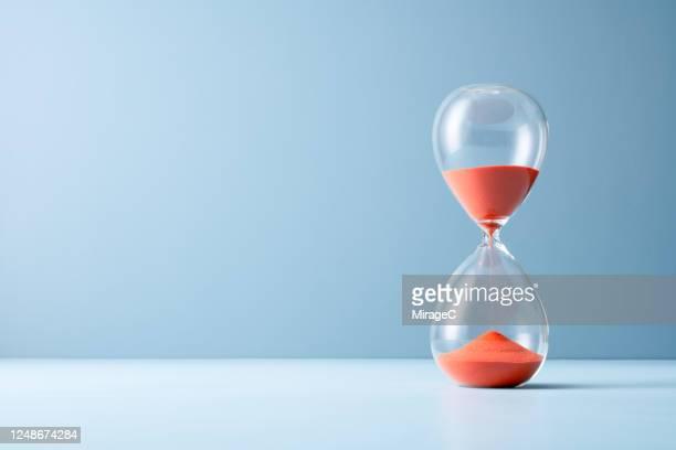 orange sand hourglass - ampulheta imagens e fotografias de stock