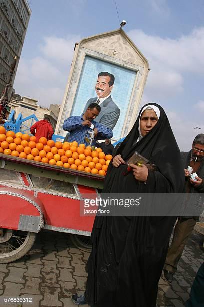 Orange sellers beneath a tile portrait of Saddam Hussein portrait Photo by Jason Florio/Corbis