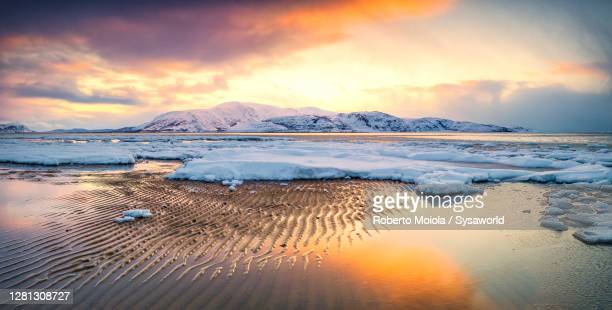 orange sky at sunset over the icy sea in winter, finnmark, norway - polar stock pictures, royalty-free photos & images