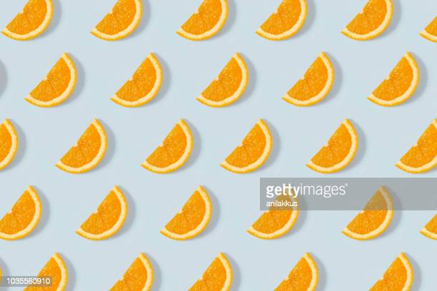orange slice pattern on blue background - arancione foto e immagini stock