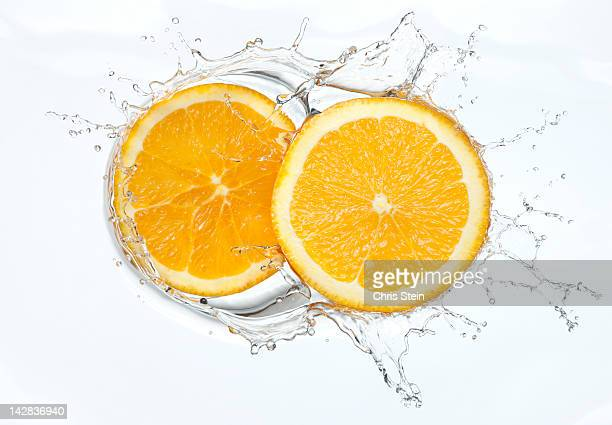 orange slices splash - zitrusfrucht stock-fotos und bilder