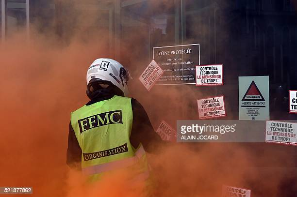Orange smoke from a flare rises around a protester wearing a 'Federation Francaise des Motards en Colere' vest putting stickers on a window at an...