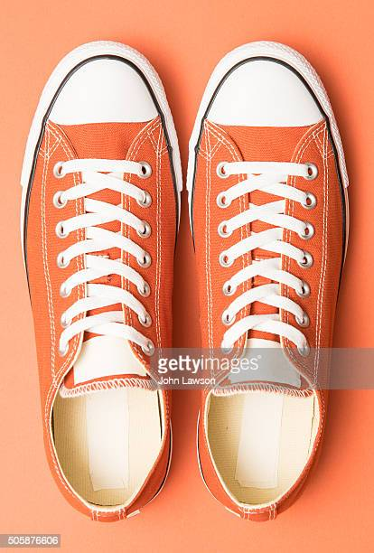 orange sneakers on an orange background - orange shoe stock photos and pictures