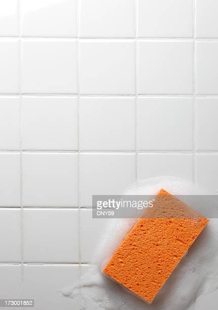 Orange soapy sponge on white bathroom tiles