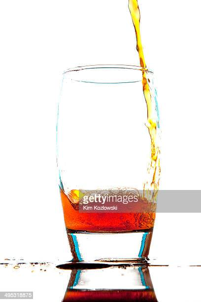Orange soda pouring into a clear glass