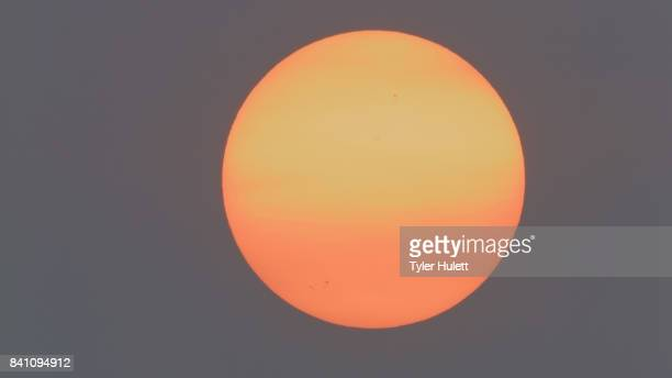 orange sunrise and sunspots due to wildfire smoke - suns stock photos and pictures
