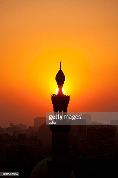 orange sunset behind silhouette of mosque and town - eid mubarak stock pictures, royalty-free photos & images