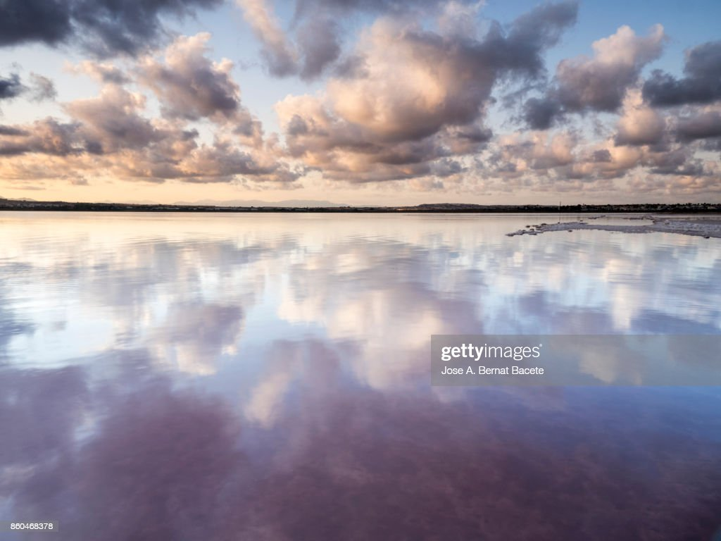 Orange sunset with high clouds, over a lake of calm water with reflection of clouds in the water. Torrevieja, (Valencian Community), Spain. : Stock Photo