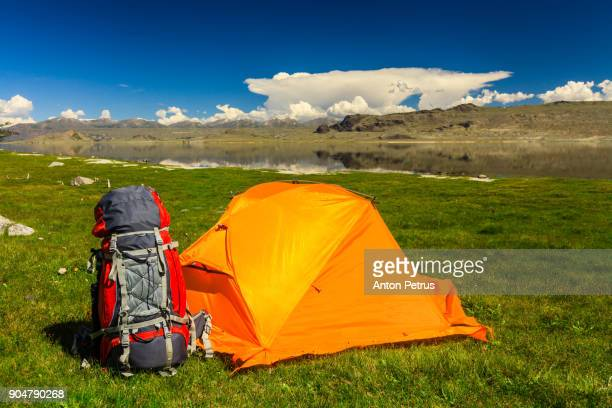 Orange tent and backpack on the shore of a mountain lake