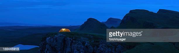 Orange tent glowing in blue mountain wilderness Scotland