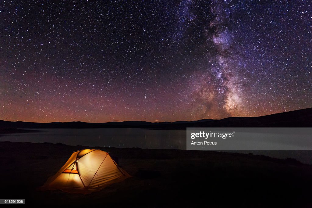 Orange tent in the mountains at night : Stock Photo