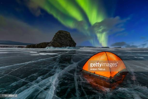 orange tent on the ice of a lake in winter under the northern lights - travel destinations stock pictures, royalty-free photos & images