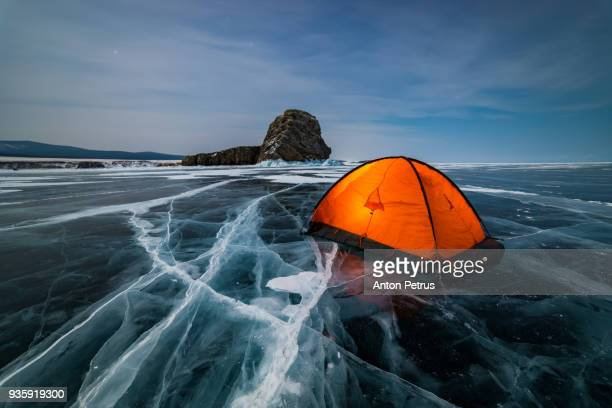Orange tent on the ice of Lake Baikal at night