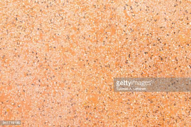 Orange terrazzo flooring with flecks texture background pattern