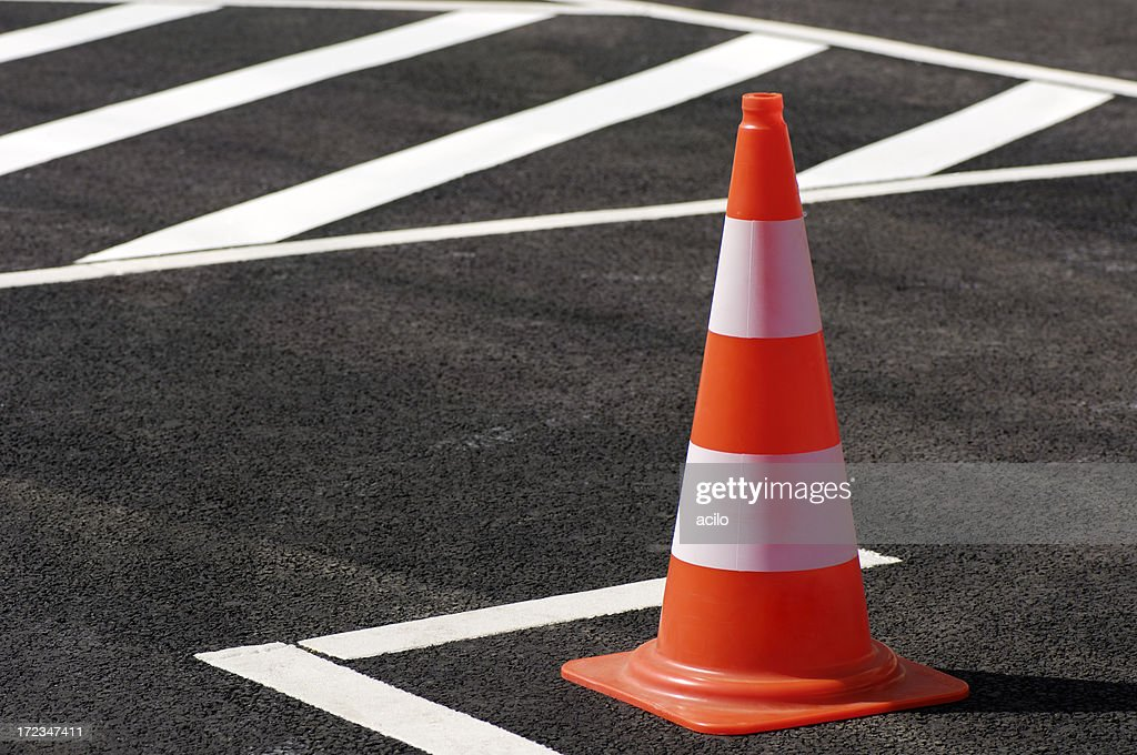Orange traffic cone sitting on the black top pavement : Stock Photo