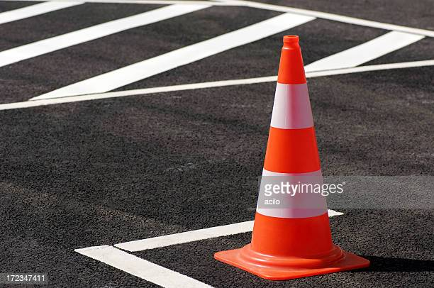 orange traffic cone sitting on the black top pavement - cone shape stock photos and pictures