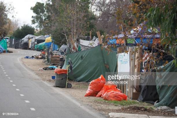 Orange trash bags sit outside tents and tarps of a homeless encampment along the Santa Ana riverbed bicycle path near Angel Stadium in Anaheim...
