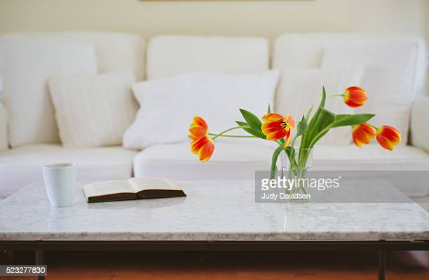 Orange tulips on a white marble coffee table with couch in background