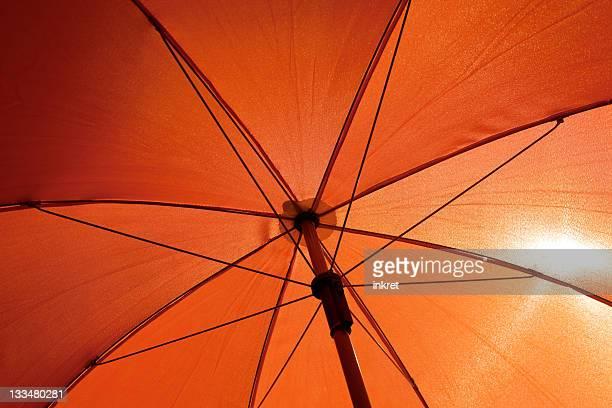 Orange umbrella from underneath with sun shining through